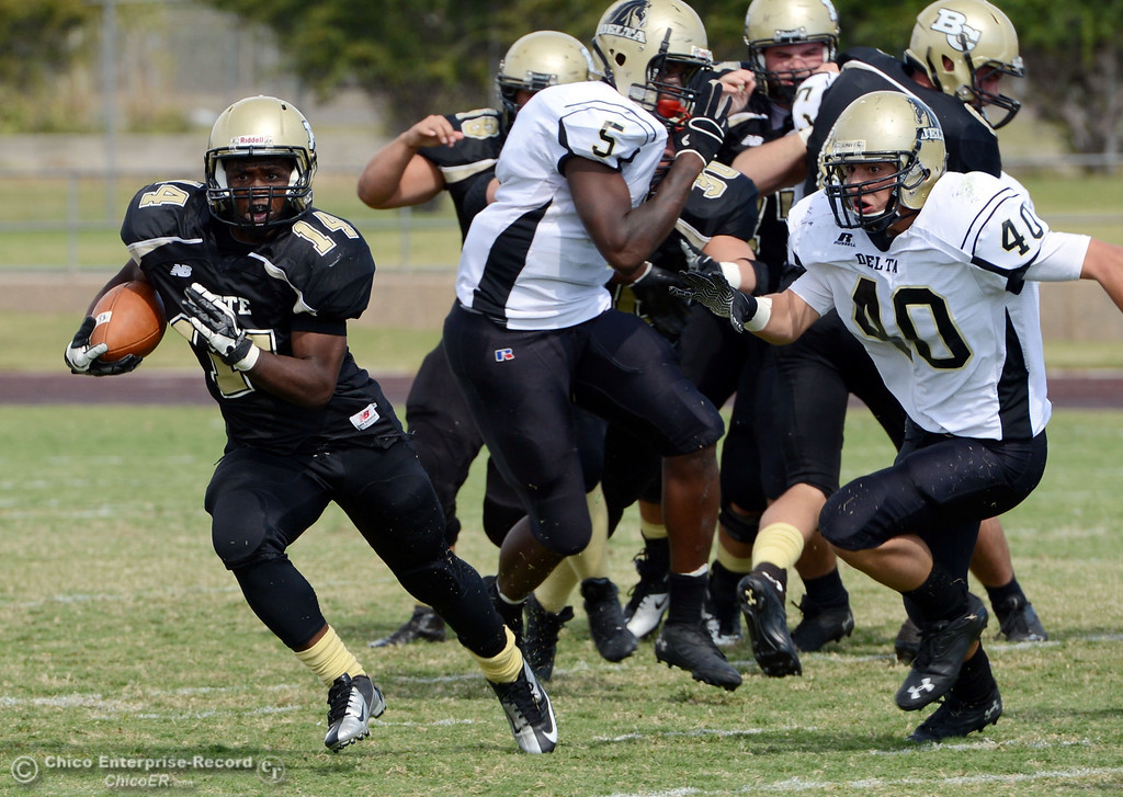 . Butte College\'s #14 Robert Frazier (left) rushes on a block against Delta College\'s #40 Adrian Ramos (right) in the second quarter of their football game at Butte\'s Cowan Stadium Saturday, September 28, 2013, in Oroville, Calif.  (Jason Halley/Chico Enterprise-Record)