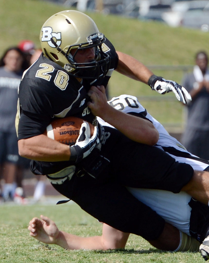 . Butte College\'s #20 Armand Bokitch (left) is tackled against Delta College\'s #50 Tyler Huckaby (right) in the second quarter of their football game at Butte\'s Cowan Stadium Saturday, September 28, 2013, in Oroville, Calif.  (Jason Halley/Chico Enterprise-Record)