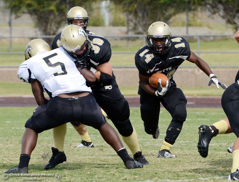 . Butte College\'s #14 Robert Frazier (right) rushes on a block by #30 Eric DeLucchi (center) against Delta College\'s #5 DaShaun Perkins (left) in the second quarter of their football game at Butte\'s Cowan Stadium Saturday, September 28, 2013, in Oroville, Calif.  (Jason Halley/Chico Enterprise-Record)
