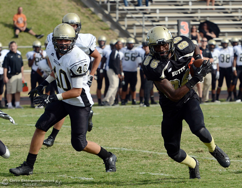 . Butte College\'s #86 Jon Parks (right) rushes for a touchdown against Delta College\'s #40 Adrian Ramos (left) in the fourth quarter of their football game at Butte\'s Cowan Stadium Saturday, September 28, 2013, in Oroville, Calif.  (Jason Halley/Chico Enterprise-Record)