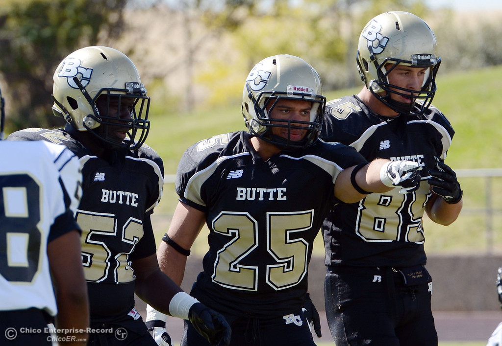 . Butte College\'s #52 Kyjuan Tate, #25 De\'Aundray Gooden, and #85 Richard Murphy (left to right)  against Delta College in the first quarter of their football game at Butte\'s Cowan Stadium Saturday, September 28, 2013, in Oroville, Calif.  (Jason Halley/Chico Enterprise-Record)