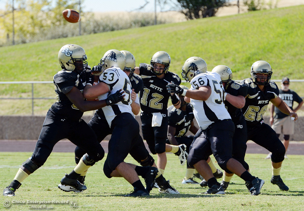 . Butte College\'s #12 Thomas Stuart (center) throws a pass against Delta College in the first quarter of their football game at Butte\'s Cowan Stadium Saturday, September 28, 2013, in Oroville, Calif.  (Jason Halley/Chico Enterprise-Record)