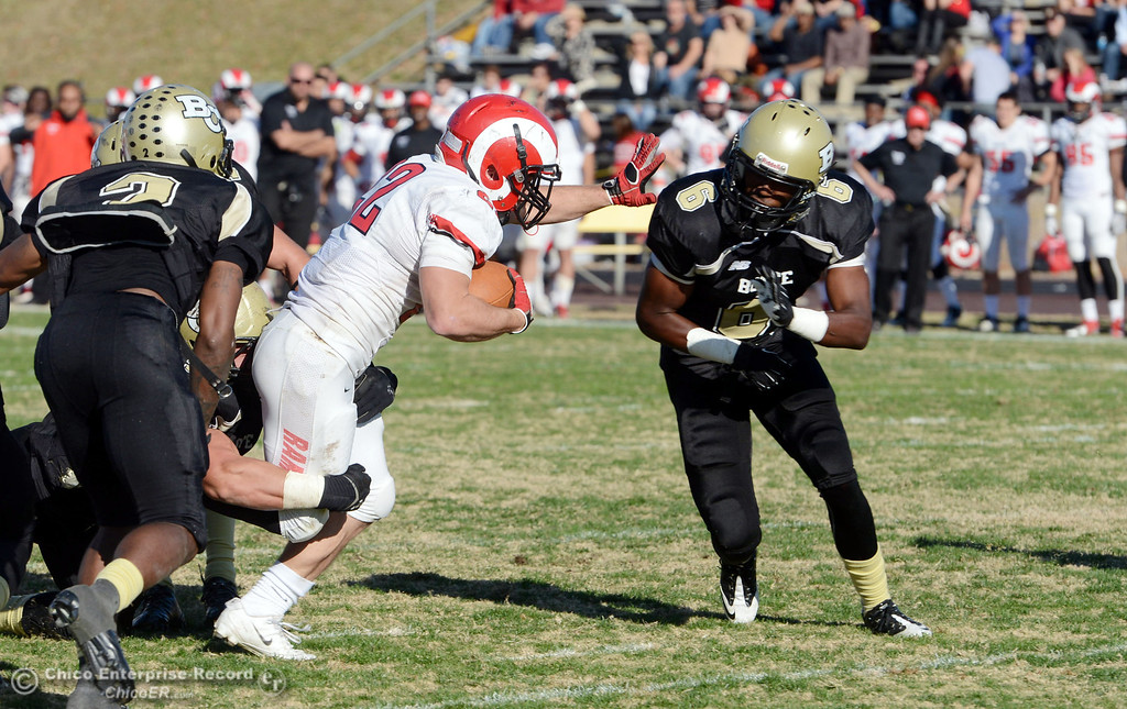 . Butte College\'s #9 Tyler Adair (left) and #6 Denzel Conyers (right) tackle against Fresno City College\'s #22 Alek Mechikoff (center) in the third quarter of their football game at Butte\'s Cowan Stadium Saturday, November 30, 2013 in Butte Valley, Calif.  (Jason Halley/Chico Enterprise-Record)