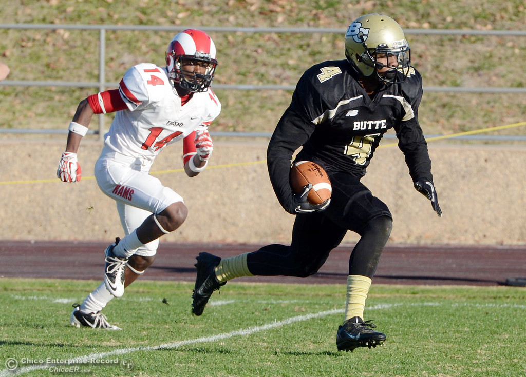 . Butte College\'s #4 Chris Edwards (right) runs back an interception against Fresno City College\'s #14 Darius Armstead (left) in the fourth quarter of their football game at Butte\'s Cowan Stadium Saturday, November 30, 2013 in Butte Valley, Calif.  (Jason Halley/Chico Enterprise-Record)