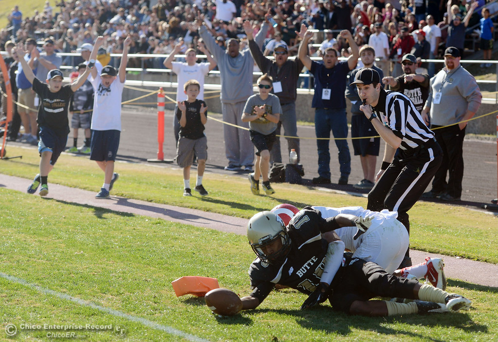 . Butte College\'s #10 CJ Grice (left) scored a touchdown against Fresno City College\'s #8 Justice Sarcedo (right) in the first quarter of their football game at Butte\'s Cowan Stadium Saturday, November 30, 2013 in Butte Valley, Calif.  (Jason Halley/Chico Enterprise-Record)
