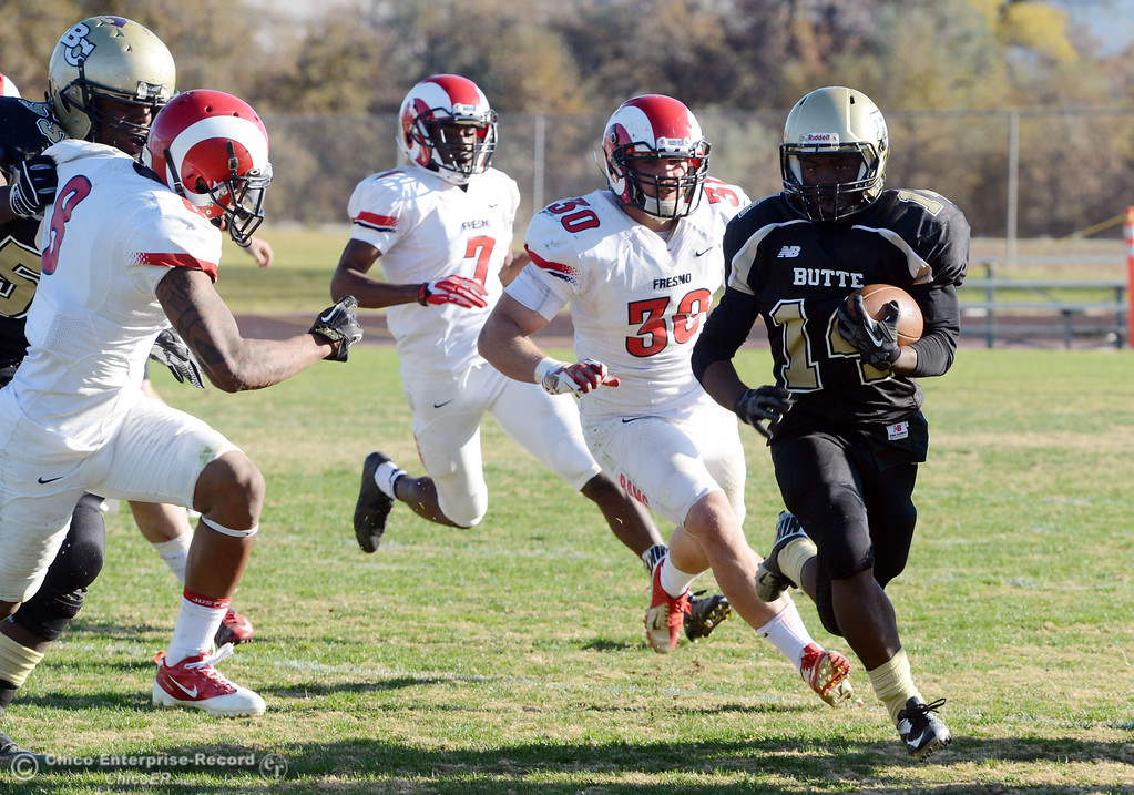 . Butte College\'s #14 Robert Frazier (right) rushes against Fresno City College\'s #30 Tyler Bates, #7 Vadal McDonald, and #8 Justice Sarcedo (left to right) in the third quarter of their football game at Butte\'s Cowan Stadium Saturday, November 30, 2013 in Butte Valley, Calif.  (Jason Halley/Chico Enterprise-Record)