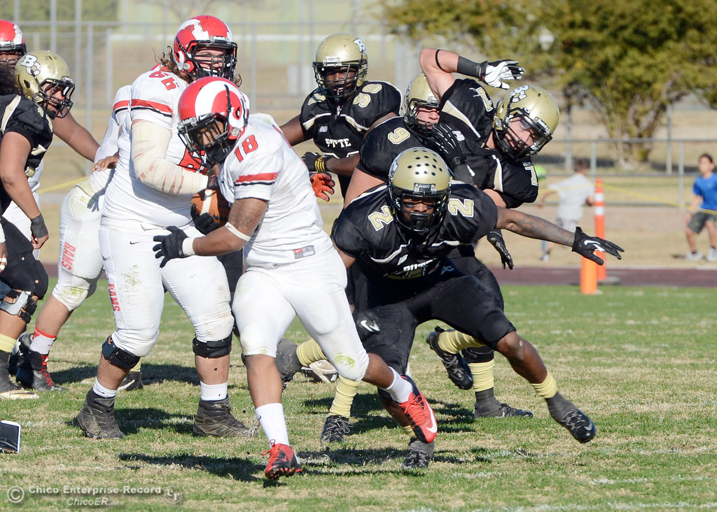 . Butte College\'s #2 Deonte Flemings (right) tackle against Fresno City College\'s #18 Micah Ledezma (left) in the third quarter of their football game at Butte\'s Cowan Stadium Saturday, November 30, 2013 in Butte Valley, Calif.  (Jason Halley/Chico Enterprise-Record)