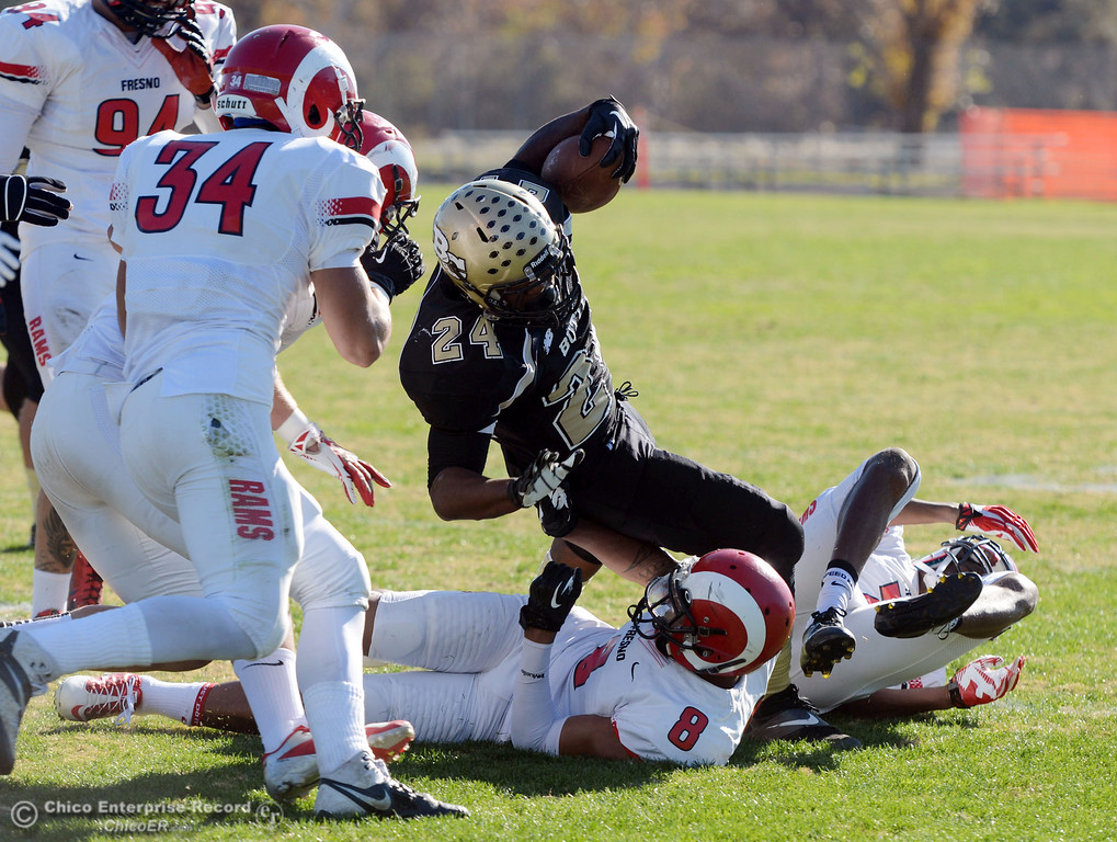 . Butte College\'s #24 Kendall Williams (top) is tackled against Fresno City College\'s #8 Justice Sarcedo (bottom) in the first quarter of their football game at Butte\'s Cowan Stadium Saturday, November 30, 2013 in Butte Valley, Calif.  (Jason Halley/Chico Enterprise-Record)