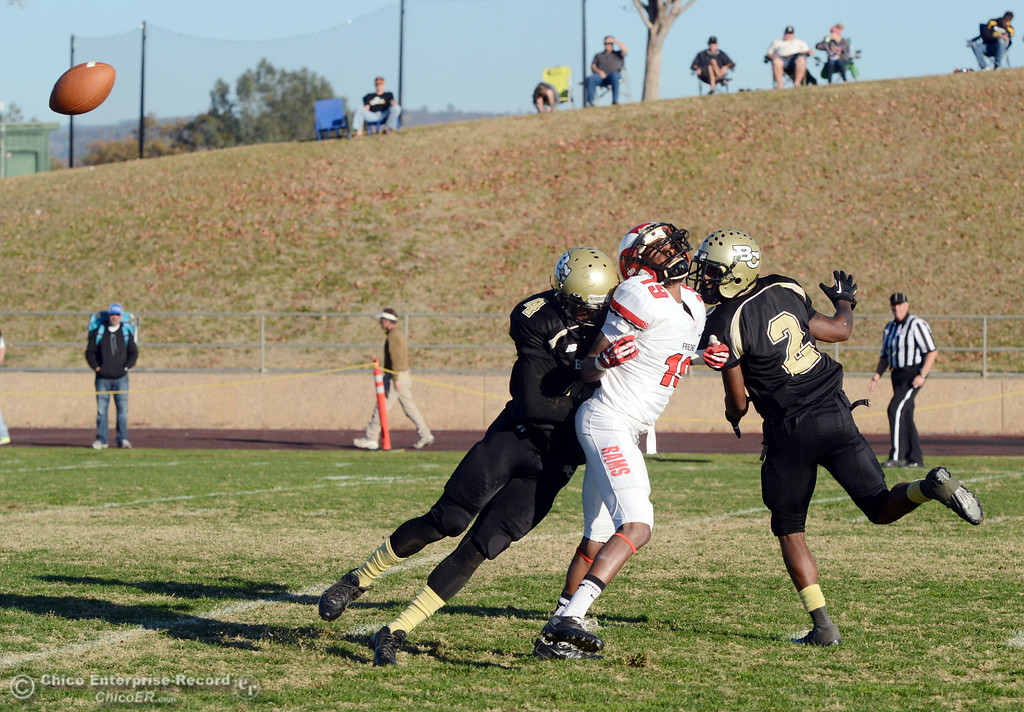 . Butte College\'s #4 Chris Edwards (left) lays a hit against Fresno City College\'s #19 Ian Charles (center) as #2 Deonte Flemings (right) looks on in the fourth quarter of their football game at Butte\'s Cowan Stadium Saturday, November 30, 2013 in Butte Valley, Calif.  (Jason Halley/Chico Enterprise-Record)