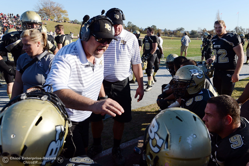 . Butte College coach Willie Thomas (left) talks to the team against Fresno City College in the third quarter of their football game at Butte\'s Cowan Stadium Saturday, November 30, 2013 in Butte Valley, Calif.  (Jason Halley/Chico Enterprise-Record)