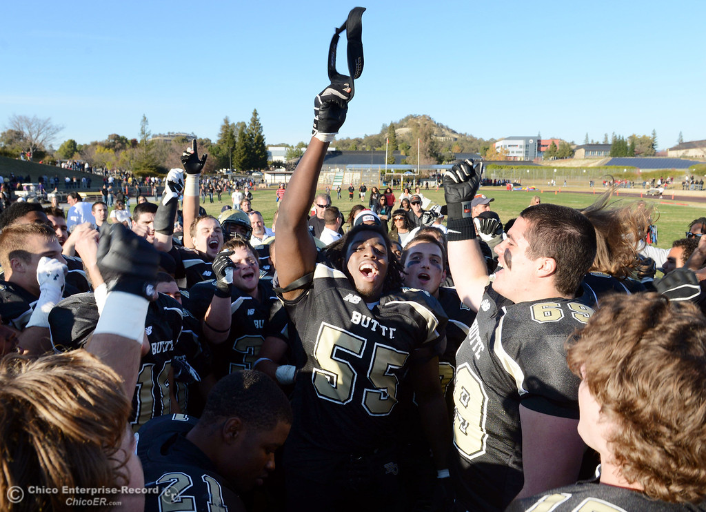 . Butte College\'s #55 Dominique Harris (center) leads the team in a cheer to celebrate their win against Fresno City College at the end of their football game at Butte\'s Cowan Stadium Saturday, November 30, 2013 in Butte Valley, Calif.  (Jason Halley/Chico Enterprise-Record)
