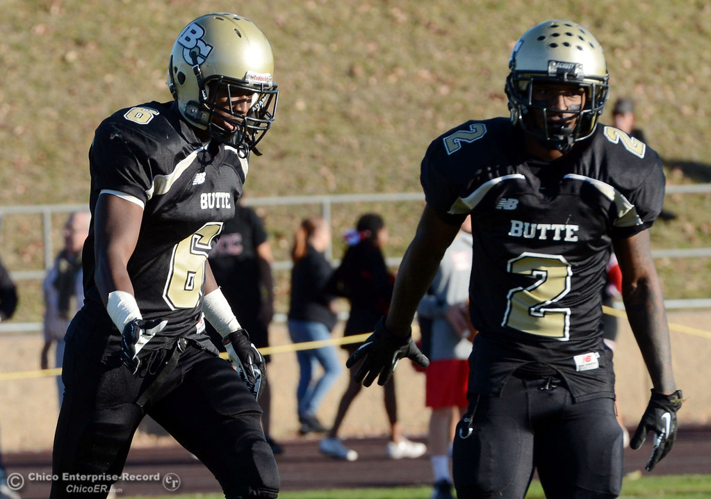 . Butte College\'s #6 Denzel Conyers (left) high-fives #2 Deonte Flemings (right) against Fresno City College in the fourth quarter of their football game at Butte\'s Cowan Stadium Saturday, November 30, 2013 in Butte Valley, Calif.  (Jason Halley/Chico Enterprise-Record)