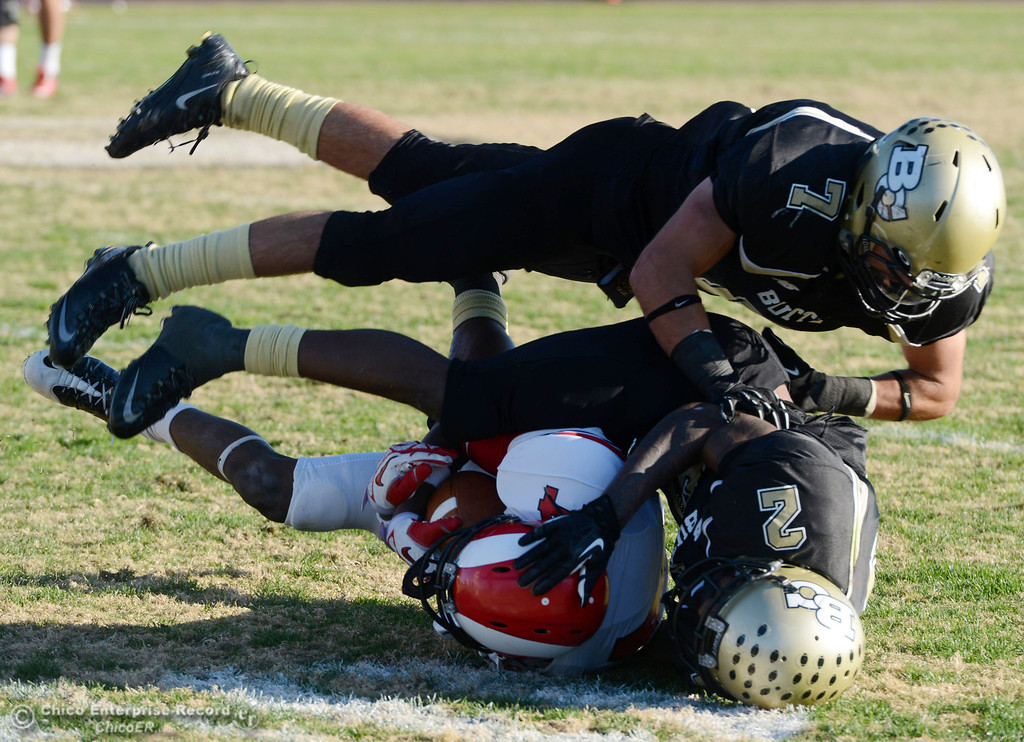 . Butte College\'s #2 Deonte Flemings (right) and #7 Ryan Holland (top) tackle against Fresno City College\'s #14 Darius Armstead (left) in the fourth quarter of their football game at Butte\'s Cowan Stadium Saturday, November 30, 2013 in Butte Valley, Calif.  (Jason Halley/Chico Enterprise-Record)