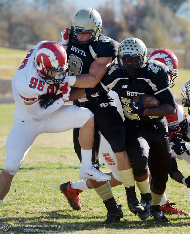 . Butte College\'s #24 Kendall Williams (right) rushes on a block by #8 Bo Brummel (center) against Fresno City College\'s #96 Mathew Valdez (left) in the first quarter of their football game at Butte\'s Cowan Stadium Saturday, November 30, 2013 in Butte Valley, Calif.  (Jason Halley/Chico Enterprise-Record)