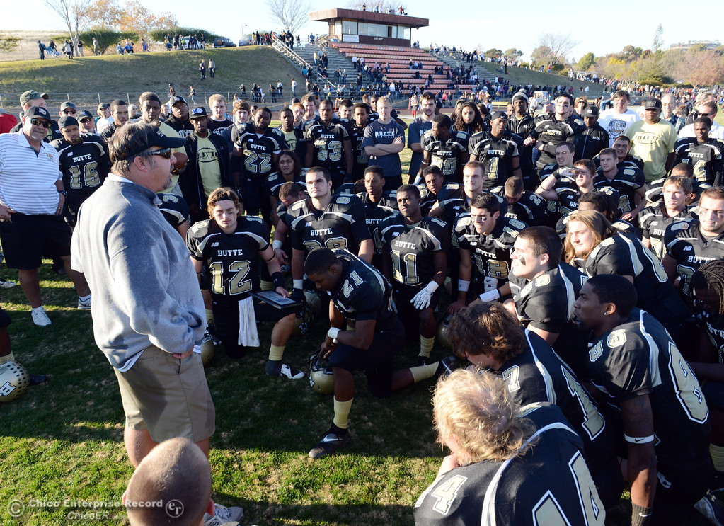 . Butte College head coach Jeff Jordan (left) talks to the team in their win against Fresno City College at the end of their football game at Butte\'s Cowan Stadium Saturday, November 30, 2013 in Butte Valley, Calif.  (Jason Halley/Chico Enterprise-Record)
