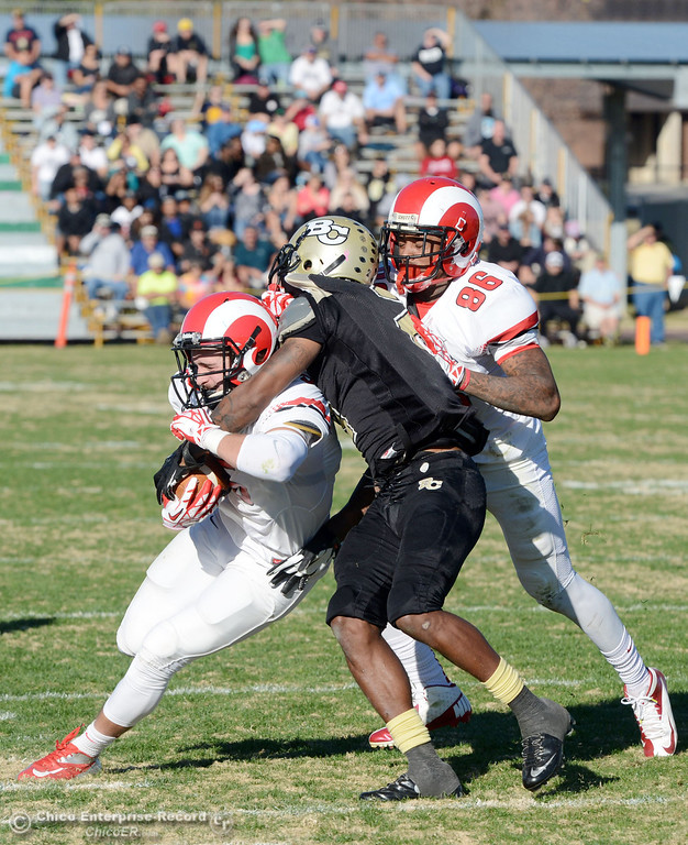 . Butte College\'s #2 Deonte Flemings (center) tackles against Fresno City College\'s #5 Brayden Sanchez (left) near #86 Kevin Beckwith (right) in the third quarter of their football game at Butte\'s Cowan Stadium Saturday, November 30, 2013 in Butte Valley, Calif.  (Jason Halley/Chico Enterprise-Record)