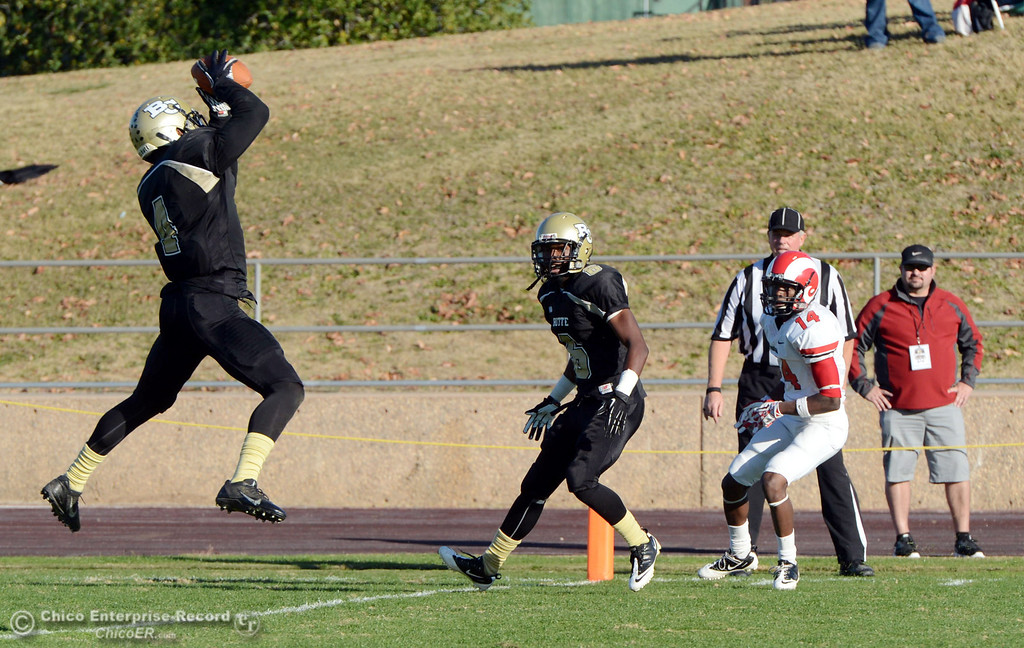 . Butte College\'s #4 Chris Edwards (left) picks up an interception as #6 Denzel Conyers (center) looks on against Fresno City College\'s #14 Darius Armstead (right) in the fourth quarter of their football game at Butte\'s Cowan Stadium Saturday, November 30, 2013 in Butte Valley, Calif.  (Jason Halley/Chico Enterprise-Record)