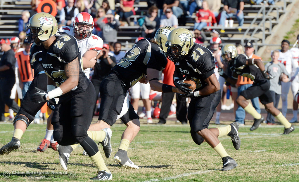 . Butte College\'s #12 Thomas Stuart (left) hands off to #21 Marvel Harris (right) against Fresno City College in the third quarter of their football game at Butte\'s Cowan Stadium Saturday, November 30, 2013 in Butte Valley, Calif.  (Jason Halley/Chico Enterprise-Record)