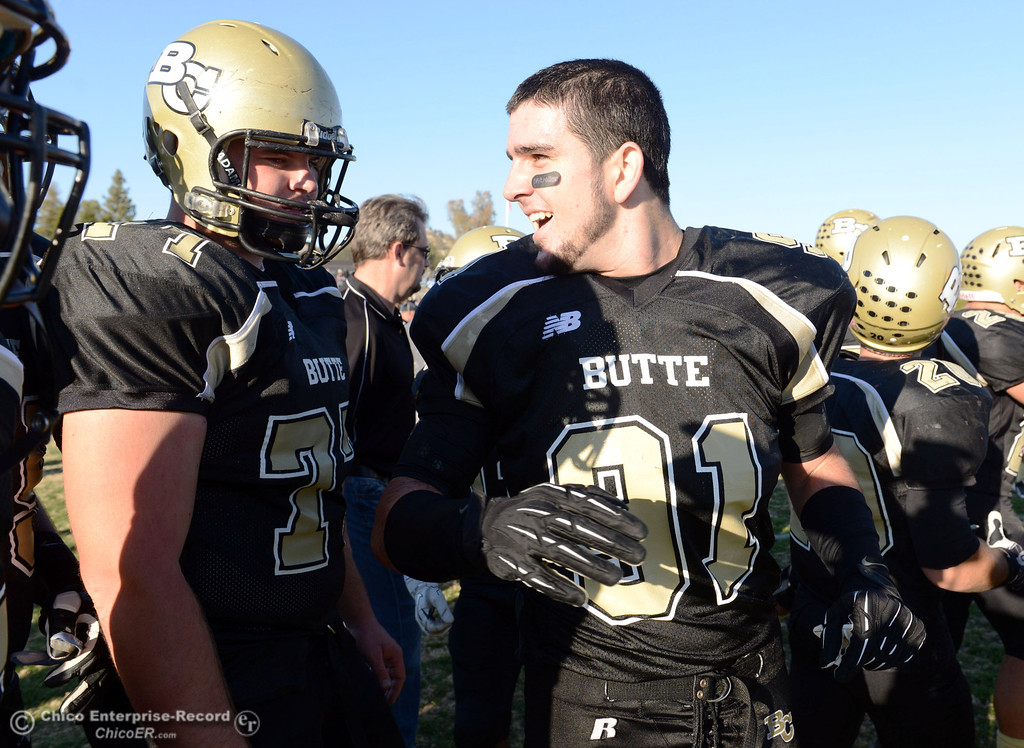 . Butte College\'s #77 Scott Batchelder (left) and #91 Mike Fratianni celebrates a win against Fresno City College at the end of their football game at Butte\'s Cowan Stadium Saturday, November 30, 2013 in Butte Valley, Calif.  (Jason Halley/Chico Enterprise-Record)