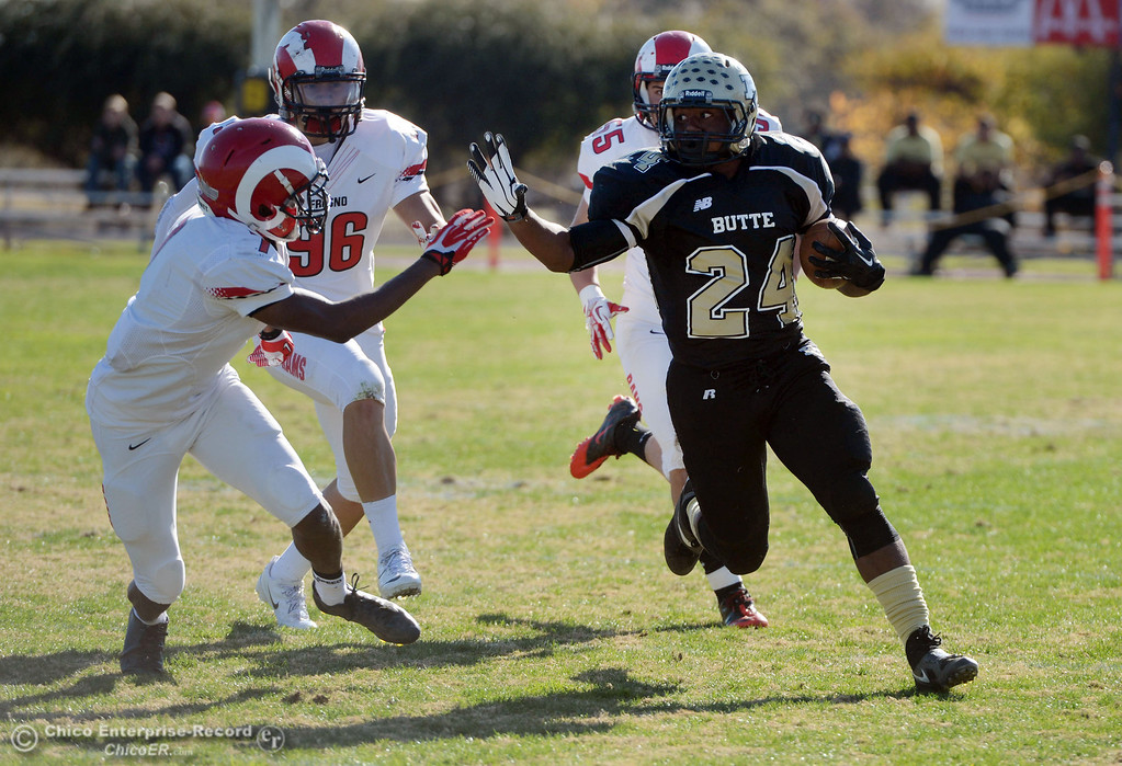 . Butte College\'s #24 Kendall Williams (right) rushes against Fresno City College\'s #7 Vadal McDonald (left) in the first quarter of their football game at Butte\'s Cowan Stadium Saturday, November 30, 2013 in Butte Valley, Calif.  (Jason Halley/Chico Enterprise-Record)