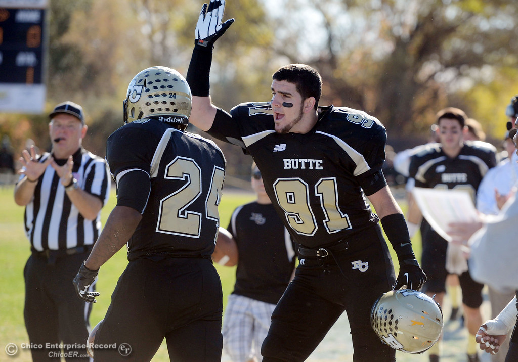 . Butte College\'s #91 Mike Fratianni (right) cheers on #24 Kendall Williams (left) against Fresno City College in the first quarter of their football game at Butte\'s Cowan Stadium Saturday, November 30, 2013 in Butte Valley, Calif.  (Jason Halley/Chico Enterprise-Record)