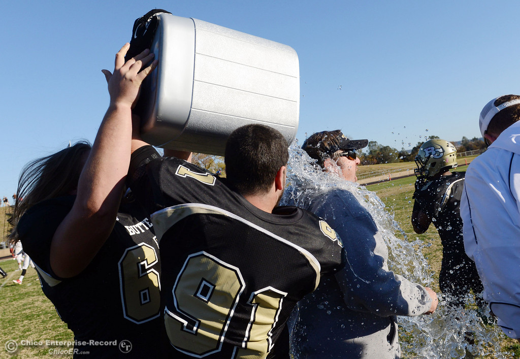 . Butte College\'s #65 Tyler Anglin (left) and #91 Mike Fratianni (center) dump water on head coach Jeff Jordan (right) against Fresno City College at the end of their football game at Butte\'s Cowan Stadium Saturday, November 30, 2013 in Butte Valley, Calif.  (Jason Halley/Chico Enterprise-Record)