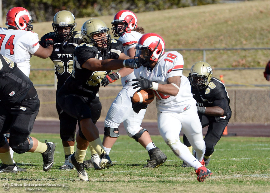 . Butte College\'s #99 Leopeni Siania (left) defends against Fresno City College\'s #18 Micah Ledezma (right) in the second quarter of their football game at Butte\'s Cowan Stadium Saturday, November 30, 2013 in Butte Valley, Calif.  (Jason Halley/Chico Enterprise-Record)