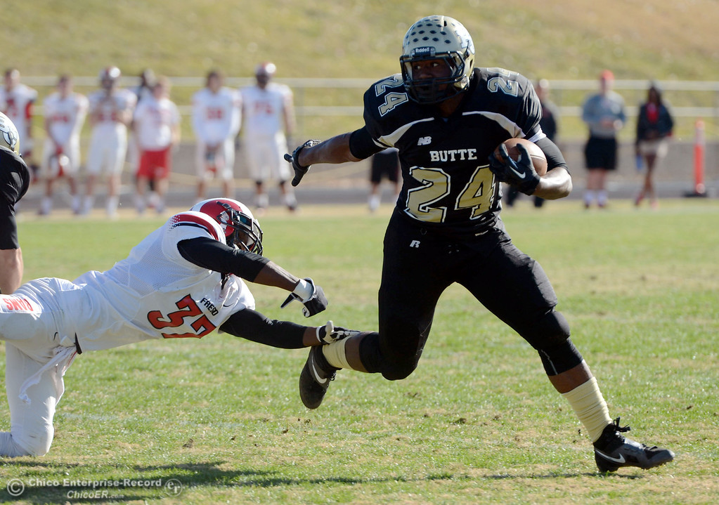 . Butte College\'s #24 Kendall Williams (right) rushes against Fresno City College\'s #37 Gerald Nutt (left) in the first quarter of their football game at Butte\'s Cowan Stadium Saturday, November 30, 2013 in Butte Valley, Calif.  (Jason Halley/Chico Enterprise-Record)