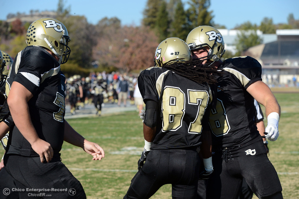 . Butte College\'s #8 Bo Brummel (right) celebrates a touchdown by #87 Timazray Shepherd (center) against Fresno City College in the second quarter of their football game at Butte\'s Cowan Stadium Saturday, November 30, 2013 in Butte Valley, Calif.  (Jason Halley/Chico Enterprise-Record)