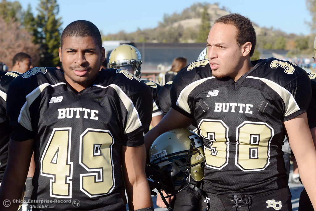 . Butte College\'s #49 Sean Mardis (left) and #38 Marcus McDonald (right) on the sidelines against Fresno City College in the third quarter of their football game at Butte\'s Cowan Stadium Saturday, November 30, 2013 in Butte Valley, Calif.  (Jason Halley/Chico Enterprise-Record)