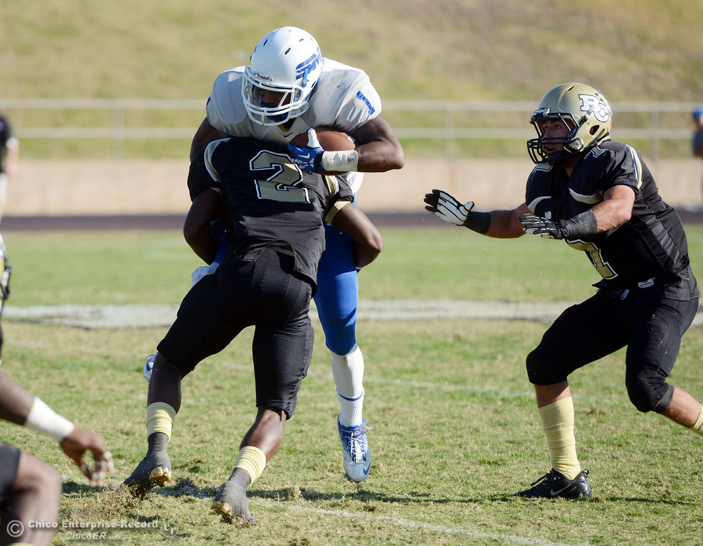 . Butte College\'s #2 Deonte Flemings (left) tackles against College of San Mateo\'s #1 Quincy Nelson (center) as Butte\'s #7 Ryan Holland (right) looks on in the third quarter of their football game at Butte\'s Cowan Stadium Saturday, November 2, 2013 in Oroville, Calif.  (Jason Halley/Chico Enterprise-Record)