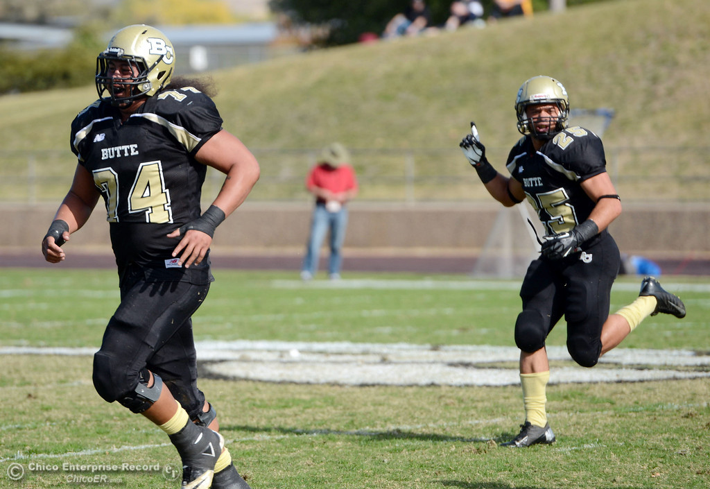 . Butte College\'s #74 Christopher Siliga (left) and #25 Gooden De\'Aundray (right) react to a tackle against San Mateo College in the first quarter of their football game at Butte\'s Cowan Stadium Saturday, November 2, 2013 in Oroville, Calif.  (Jason Halley/Chico Enterprise-Record)