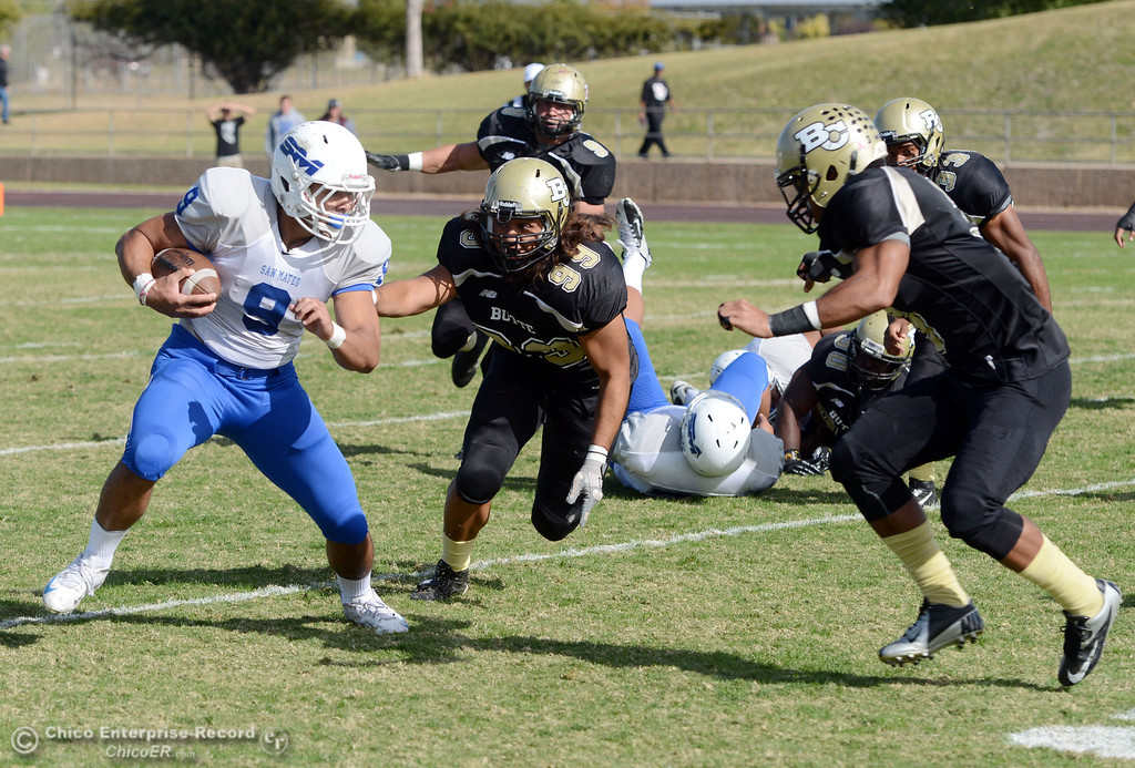 . Butte College\'s #99 Leopeni Siania (center) and #3 London Muse (right) tackle against San Mateo College\'s #9 George Naufahu (left) in the first quarter of their football game at Butte\'s Cowan Stadium Saturday, November 2, 2013 in Oroville, Calif.  (Jason Halley/Chico Enterprise-Record)