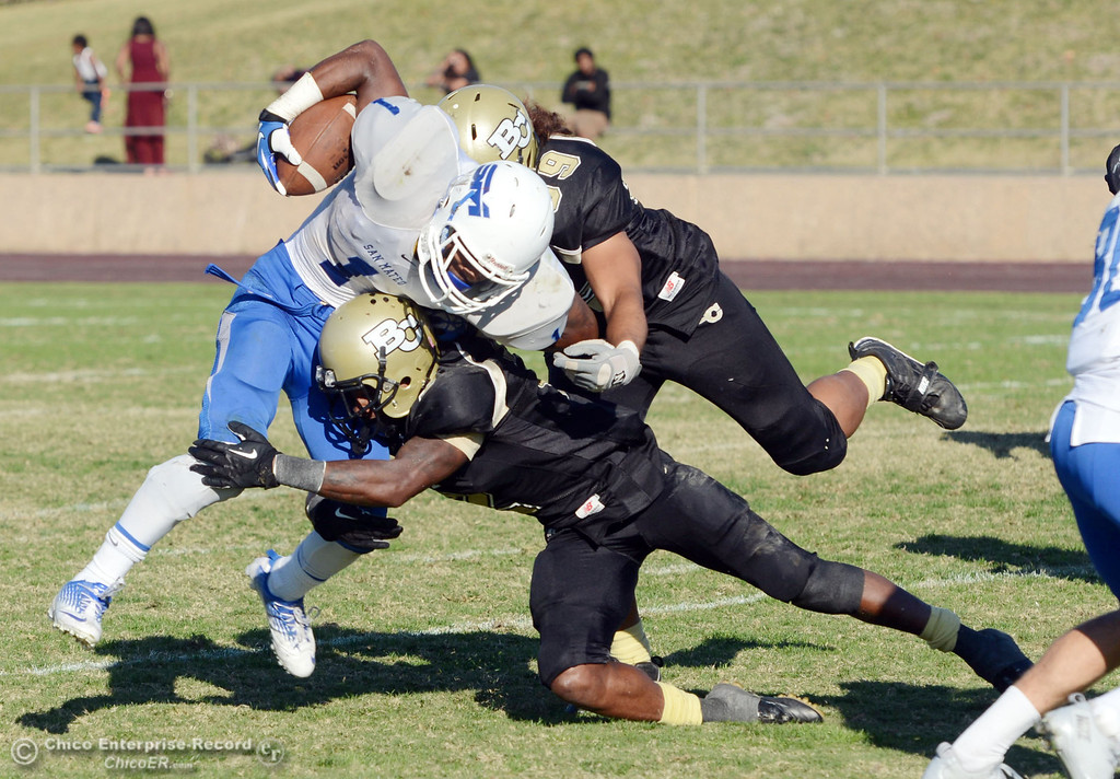 . Butte College\'s #99 Leopeni Siania (top) and #2 Deonte Flemings (bottom) tackle against College of San Mateo\'s #1 Quincy Nelson (left) in the fourth quarter of their football game at Butte\'s Cowan Stadium Saturday, November 2, 2013 in Oroville, Calif.  (Jason Halley/Chico Enterprise-Record)