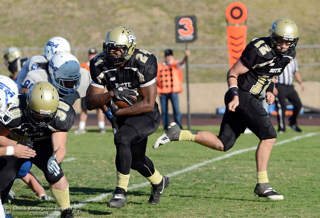 . Butte College\'s #24 Kendall Williams (left) rushes on a hand off from #12 Thomas Stuart (right) against College of San Mateo in the fourth quarter of their football game at Butte\'s Cowan Stadium Saturday, November 2, 2013 in Oroville, Calif.  (Jason Halley/Chico Enterprise-Record)