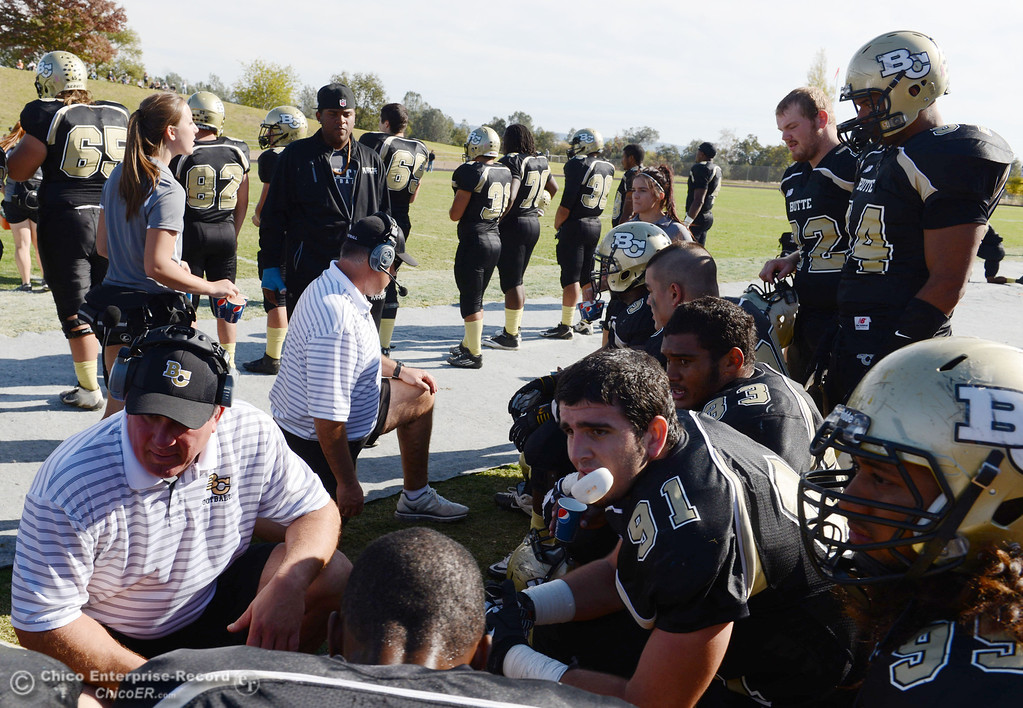 . Butte College coaches Thomas Flesher (left) and Willie Thomas (center) talk to the defense against College of San Mateo in the second quarter of their football game at Butte\'s Cowan Stadium Saturday, November 2, 2013 in Oroville, Calif.  (Jason Halley/Chico Enterprise-Record)