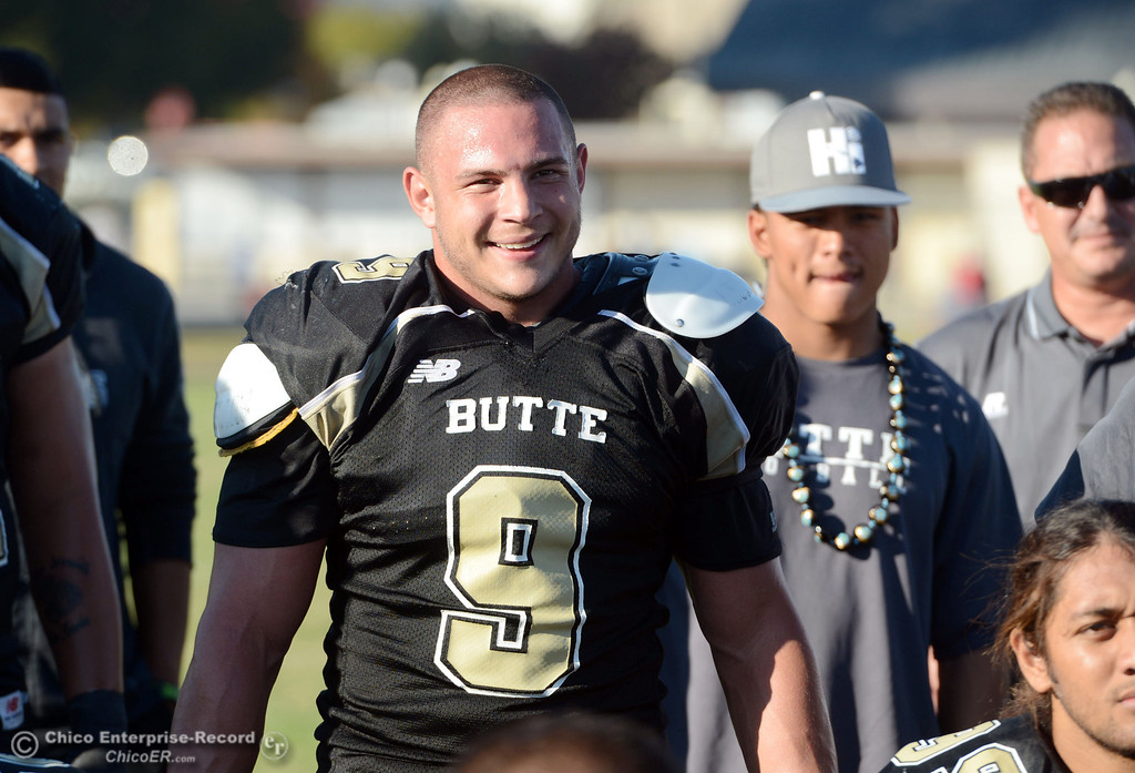 . Butte College\'s #9 Tyler Adair listens to the coach at the end of their football game against College of San Mateo at Butte\'s Cowan Stadium Saturday, November 2, 2013 in Oroville, Calif.  (Jason Halley/Chico Enterprise-Record)