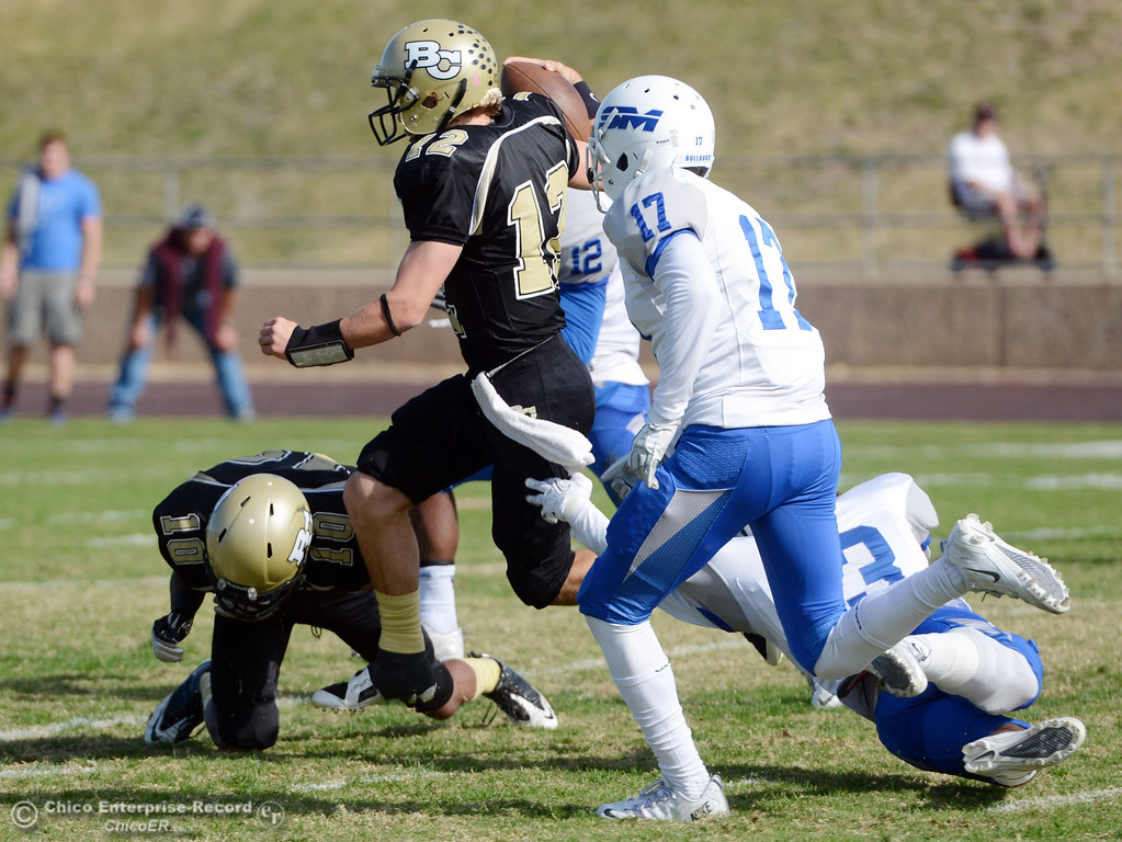 . Butte College\'s #12 Thomas Stuart (center) rushes against San Mateo College in the first quarter of their football game at Butte\'s Cowan Stadium Saturday, November 2, 2013 in Oroville, Calif.  (Jason Halley/Chico Enterprise-Record)