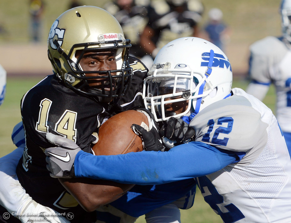 . Butte College\'s #14 Robert Frazier (left) is tackled against San Mateo College\'s #12 Taylor Mashack (right) in the third quarter of their football game at Butte\'s Cowan Stadium Saturday, November 2, 2013 in Oroville, Calif.  (Jason Halley/Chico Enterprise-Record)