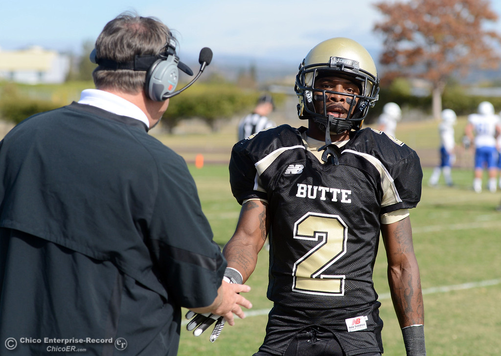 . Butte College coach Jeff Jordan (left) shakes hands with #2 Deonte Flemings (right) against San Mateo College in the first quarter of their football game at Butte\'s Cowan Stadium Saturday, November 2, 2013 in Oroville, Calif.  (Jason Halley/Chico Enterprise-Record)
