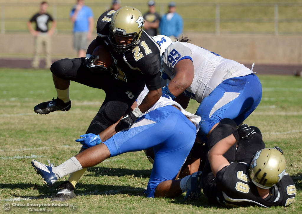 . Butte College\'s #21 Marvel Harris (left) rushes against College of San Mateo\'s #16 Michael Spivey (right) in the second quarter of their football game at Butte\'s Cowan Stadium Saturday, November 2, 2013 in Oroville, Calif.  (Jason Halley/Chico Enterprise-Record)