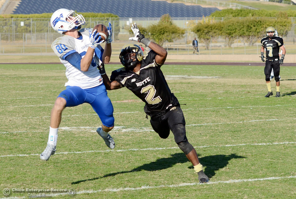 . Butte College\'s #2 Deonte Flemings (right) is unable to stop a catch against College of San Mateo\'s #80 Kevin Kutchera (left) in the fourth quarter of their football game at Butte\'s Cowan Stadium Saturday, November 2, 2013 in Oroville, Calif.  (Jason Halley/Chico Enterprise-Record)