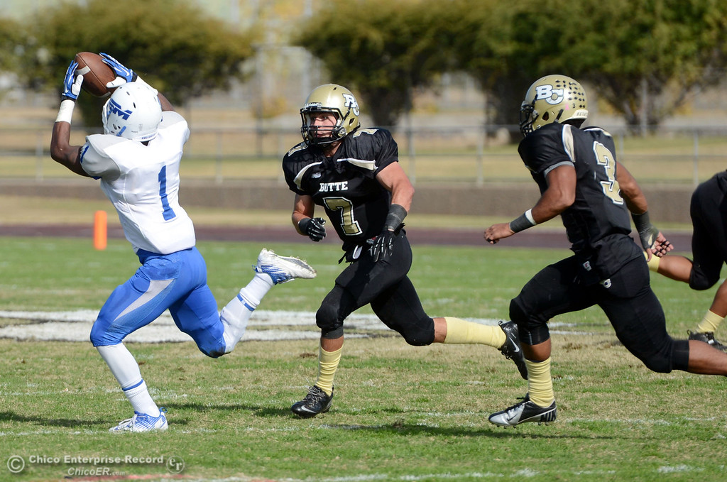 . Butte College\'s #7 Ryan Holland (center) and #3 London Muse (right) defend against at catch by San Mateo College\'s #1 Quincy Nelson (left) in the first quarter of their football game at Butte\'s Cowan Stadium Saturday, November 2, 2013 in Oroville, Calif.  (Jason Halley/Chico Enterprise-Record)