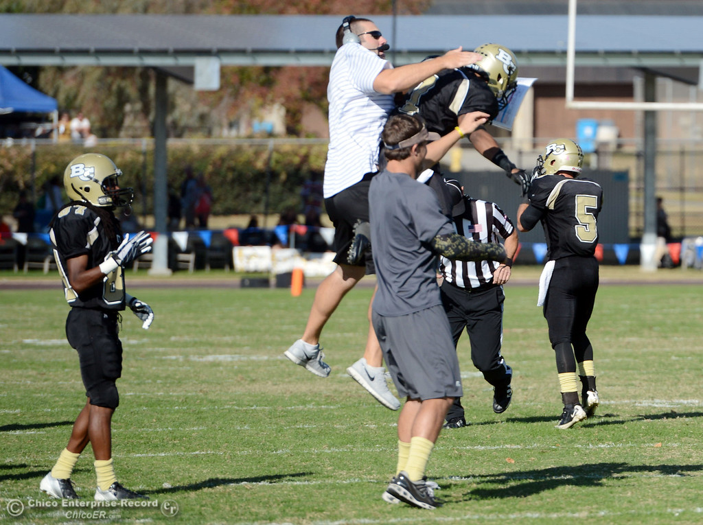 . Butte College coach Rob Snelling (left) celebrates with #1 Wes McCoy after McCoy returned a kickoff for a touchdown against San Mateo College in the third quarter of their football game at Butte\'s Cowan Stadium Saturday, November 2, 2013 in Oroville, Calif.  (Jason Halley/Chico Enterprise-Record)