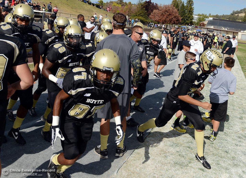 . Butte College\'s #87 Timazray Shepherd (left) and #27 Rigoberto Sanchez (right) take the field against San Mateo College in the first quarter of their football game at Butte\'s Cowan Stadium Saturday, November 2, 2013 in Oroville, Calif.  (Jason Halley/Chico Enterprise-Record)