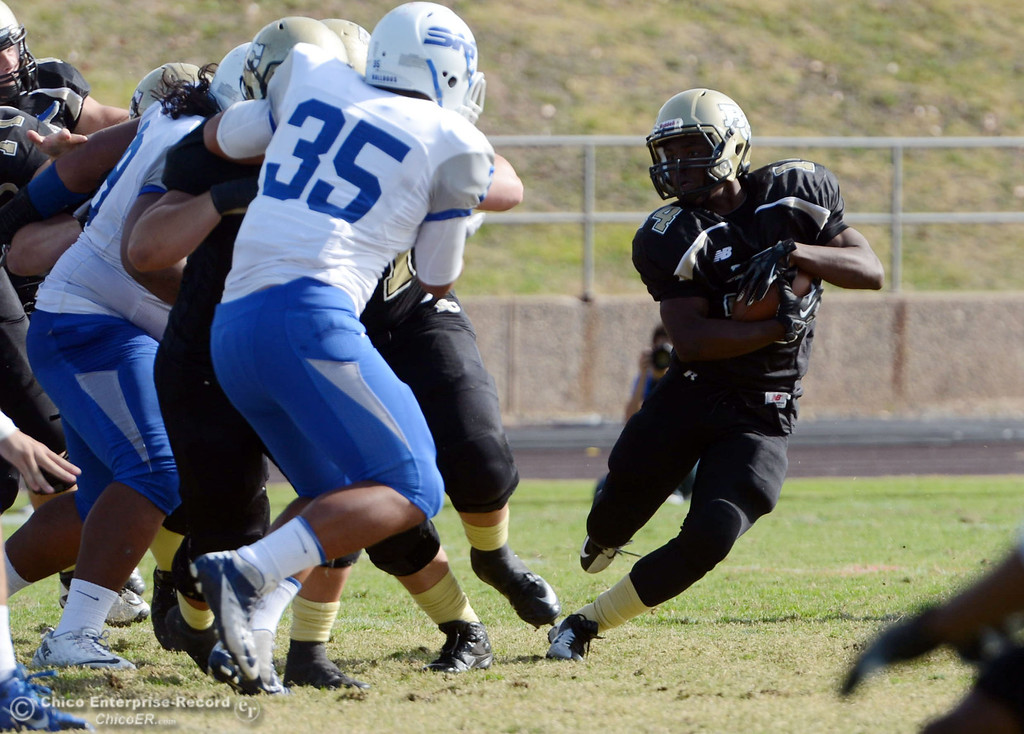. Butte College\'s #14 Robert Frazier (right) rushes against San Mateo College in the first quarter of their football game at Butte\'s Cowan Stadium Saturday, November 2, 2013 in Oroville, Calif.  (Jason Halley/Chico Enterprise-Record)