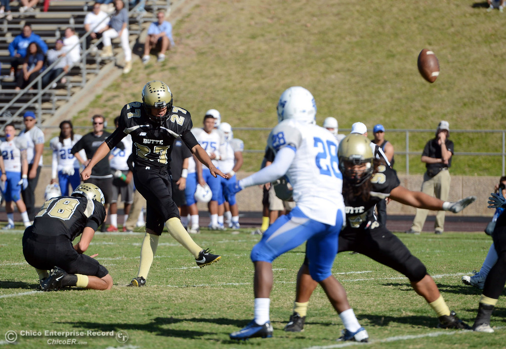 . Butte College\'s #18 Eric Ascencio (left) holds for #27 Rigoberto Sanchez to kick the extra point against College of San Mateo in the second quarter of their football game at Butte\'s Cowan Stadium Saturday, November 2, 2013 in Oroville, Calif.  (Jason Halley/Chico Enterprise-Record)