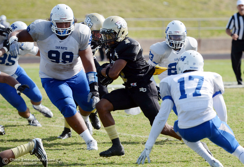 . Butte College\'s #1 Wes McCoy (center) rushes against San Mateo College\'s #99 Rika Levi, #23 Bryant Hayes and #17 Deshane Hines (left to right) in the first quarter of their football game at Butte\'s Cowan Stadium Saturday, November 2, 2013 in Oroville, Calif.  (Jason Halley/Chico Enterprise-Record)
