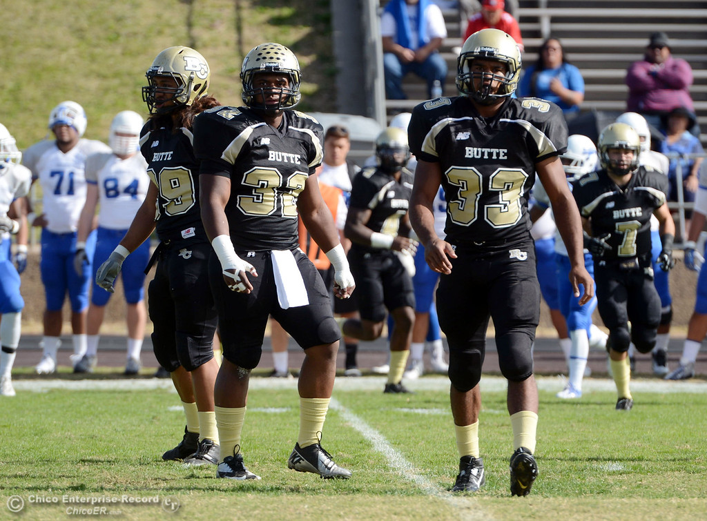 . Butte College\'s #99 Leopeni Siania, #32 Brian Anderson, and #33 Jariah Booker (left to right) against San Mateo College in the first quarter of their football game at Butte\'s Cowan Stadium Saturday, November 2, 2013 in Oroville, Calif.  (Jason Halley/Chico Enterprise-Record)