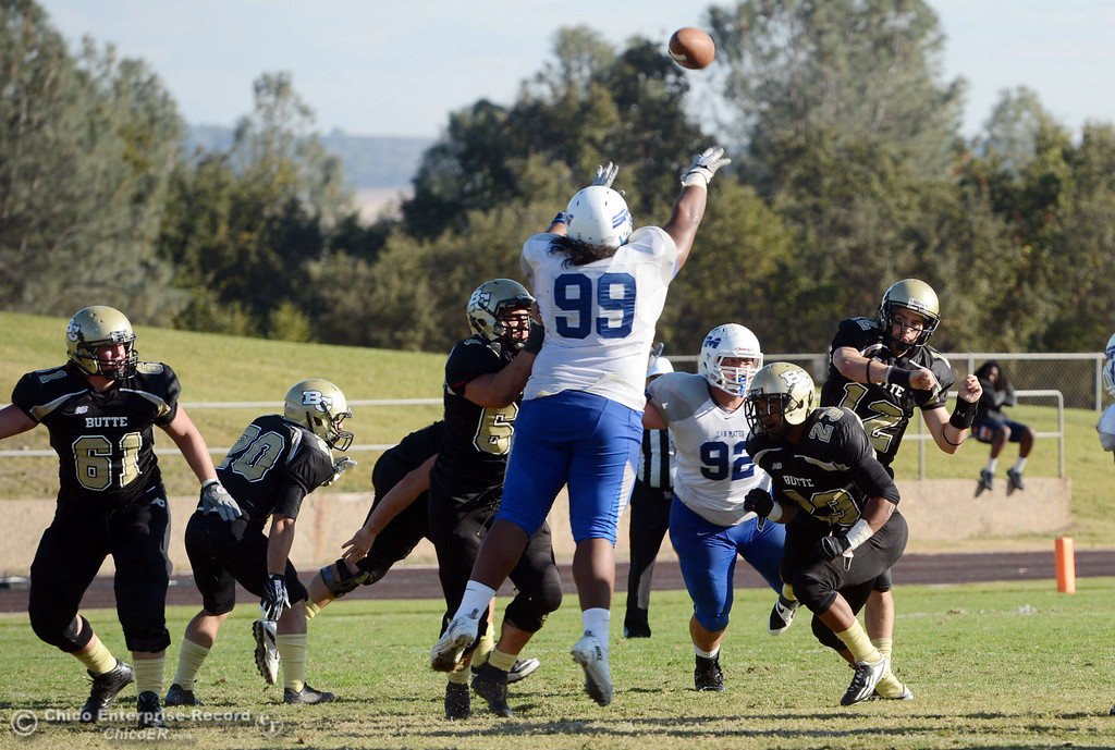 . Butte College\'s #12 Thomas Stuart (right) throws a pass against College of San Mateo\'s #99 Rika Levi (left) in the fourth quarter of their football game at Butte\'s Cowan Stadium Saturday, November 2, 2013 in Oroville, Calif.  (Jason Halley/Chico Enterprise-Record)